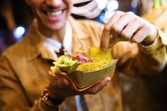Atrakcyjny młodego człowieka odwiedzać je rynek i jeść nachos w ulicie zdjęcie stock