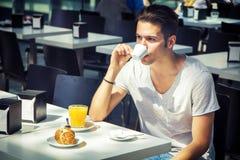 Atrakcyjny młodego człowieka s śniadanie, Pije kawę zdjęcia royalty free