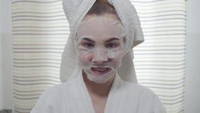 Atrakcyjny młodej kobiety łasowania ogórek z szkotową maską na jej twarzy w łazience Śliczna dziewczyna z różny barwionym zbiory