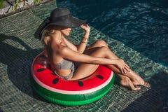 atrakcyjny młodej kobiety obsiadanie w nadmuchiwanym pierścionku przy poolside obrazy royalty free
