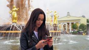 Atrakcyjny młodej kobiety odprowadzenie w parku Używać jej telefon komórkowego Elegancki str?j zdjęcie wideo