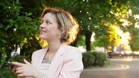 Atrakcyjny młodej kobiety odprowadzenie w uses i parku smartphone zbiory