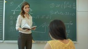 Atrakcyjny młody żeński nauczyciel na maths grupuje pozycję przed chalkboard dyskutować zdjęcie wideo