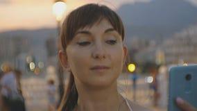 Atrakcyjny młody żeński używa smartphone Kaukaska kobieta patrzeje telefonu ekran na zmierzch halnej miejscowości wypoczynkowej z zdjęcie wideo