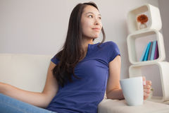 Atrakcyjny młody azjatykci kobiety obsiadanie na leżanki mienia kubku obraz stock