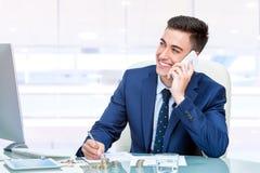 Atrakcyjny młody biznesmen opowiada na mądrze telefonie w biurze obraz stock