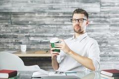 Atrakcyjny młody biznesmen przy miejscem pracy zdjęcie stock