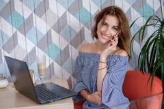 Atrakcyjny młody bizneswoman używa jej laptop i telefon przy kawiarnią fotografia stock