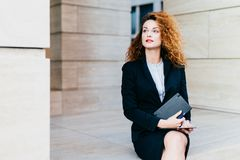 Atrakcyjny młody bizneswoman z luxuriant włosy, niebieskie oczy, czerwone wargi, będący ubranym czarnego kostium, trzymający w rę fotografia royalty free