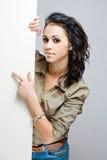 Atrakcyjny młody brunetki mienia pustego miejsca billboard. Zdjęcie Stock