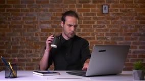 Atrakcyjny młody caucasian samiec pić kawowy i patrzeć komputer na jego pracującym miejscu wśrodku czerwonego studia