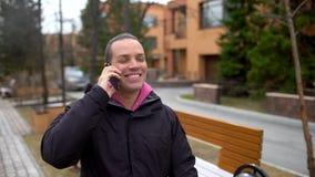 Atrakcyjny młody człowiek opowiada na jego telefonie komórkowym gdy chodzi w parku Przystojny młody człowiek opowiada na telefonu zbiory