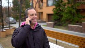 Atrakcyjny młody człowiek opowiada na jego telefonie komórkowym gdy chodzi w parku Przystojny młody człowiek opowiada na telefonu zbiory wideo