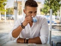 Atrakcyjny młody człowiek Pije kawę przy baru stołem obraz stock
