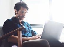 Atrakcyjny młody człowiek pracuje w domu Obsługuje używać współczesnego laptop i hełmofony w rocznika krześle podczas gdy siedząc Fotografia Royalty Free