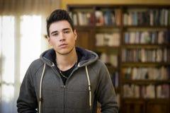 Atrakcyjny młody człowiek przed bookcase w domu obrazy royalty free