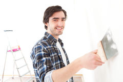Atrakcyjny młody człowiek scrubing ścianę w jego mieszkaniu Zdjęcie Stock