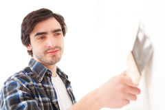 Atrakcyjny młody człowiek scrubing ścianę w jego mieszkaniu Fotografia Stock
