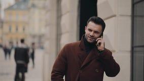 Atrakcyjny młody człowiek w eleganckim żakieta odprowadzenia puszku zatłoczona miasto ulica telefon dzwoni, on podnosi up telefon zbiory wideo