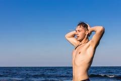 Atrakcyjny młody człowiek w morzu dostaje z wody z mokrymi brzęczeniami Zdjęcia Stock