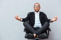 Atrakcyjny młody człowiek w szkłach medytuje na biurowym krześle Obrazy Stock