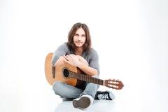 Atrakcyjny młody człowiek z długie włosy obsiadania i mienia gitarą zdjęcie stock