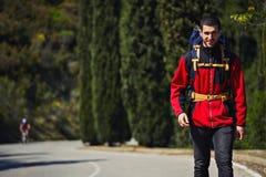 Atrakcyjny młody podróżnik iść na opustoszałej drodze i ono uśmiecha się w górach Zdjęcia Royalty Free