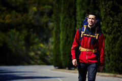 Atrakcyjny młody podróżnik iść na opustoszałej drodze w górach Obrazy Stock