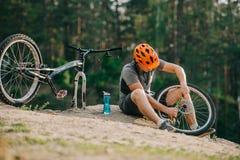 atrakcyjny młody próbny rowerzysta pompuje koło fotografia royalty free