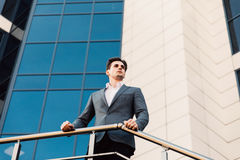 Atrakcyjny młody ufny biznesmen w klasycznym kostiumu patrzeje daleko od, opierający na balkonowej balustradzie na zewnątrz budyn Zdjęcia Stock