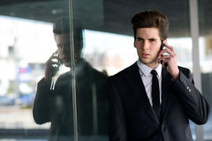Atrakcyjny młody biznesmen na telefonie w budynku biurowym Zdjęcia Royalty Free