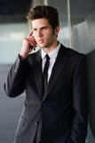 Atrakcyjny młody biznesmen na telefonie w budynku biurowym Fotografia Royalty Free