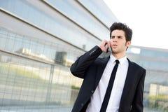 Atrakcyjny młody biznesmen na telefonie w budynku biurowym Obrazy Stock