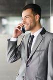 Atrakcyjny młody biznesmen na telefonie w budynku biurowym Obraz Stock