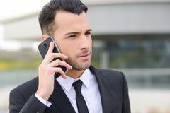 Atrakcyjny młody biznesmen na telefonie w budynku biurowym Obrazy Royalty Free