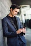 Atrakcyjny młody biznesmen na telefonie w budynku biurowym Zdjęcie Stock