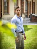 Atrakcyjny męski student collegu outdoors stoi na trawie Obrazy Royalty Free