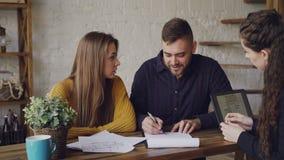 Atrakcyjny makler sprzedaje dom potomstwa dobiera się, ludzie podpisują dokumenty i chwianie ręki, pośrednik handlu nieruchomości