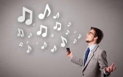 Atrakcyjny młodego człowieka śpiew, słuchanie muzyka z musicalem i Fotografia Royalty Free