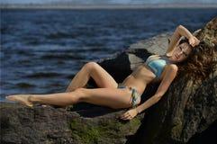 Atrakcyjny model w błękitny bikini pozować seksowny przy plażowymi skałami Obraz Royalty Free