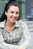 Atrakcyjny modny w średnim wieku kobiety obsiadanie w ulicznym przyglądającym zamyśleniu przy kamerą z powabnym życzliwym uśmiech obraz stock