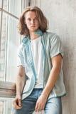 Atrakcyjny młody caucasian facet w przypadkowej odzieży salowym pobliskim okno Obrazy Stock
