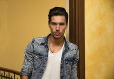 Atrakcyjny młody człowiek indoors, opierający przeciw drzwiowemu ościeżu Obrazy Royalty Free