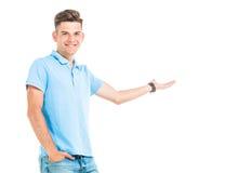 Atrakcyjny młody człowiek przedstawia coś Fotografia Royalty Free