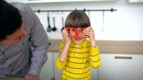 Atrakcyjny ojciec i bardzo śliczny syn mamy zabawę w kuchni w domu Zwolnione tempo Ojciec i szczęśliwa chłopiec ma zabawę podczas zbiory