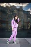 Atrakcyjny piękny potomstwo mody nastolatka modnisia dziewczyny komarnicy skok blisko miastowego ściennego tła w różowych kombine Obraz Royalty Free