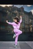 Atrakcyjny piękny potomstwo mody nastolatka modnisia dziewczyny komarnicy skok blisko miastowego ściennego tła w różowych kombine Zdjęcia Royalty Free