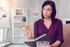 Atrakcyjny piękny skoncentrowany ciemnowłosy bizneswoman trzyma notatnika z ołówkiem obraz stock