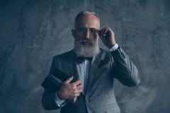 Atrakcyjny, poważny milioner w kurtce, trzyma trzy książki, obraz stock