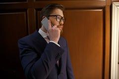 Atrakcyjny poważny skoncentrowany biznesmen opowiada telefonem zdjęcia royalty free